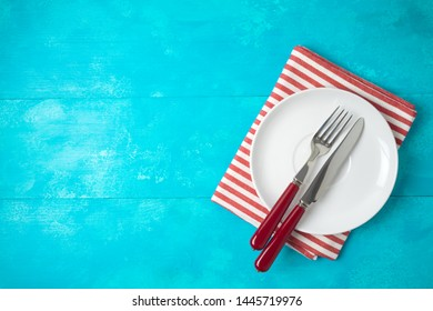 White empty plate and red striped tablecloth on blue wooden background. Top view from above