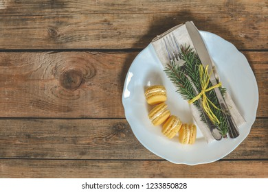 White empty plate and yellow lemon macaroon with fir tree, fork and knife tied with a ribbon on old wooden brown surface. Christmas table place setting. Holidays background, top view, cope space.