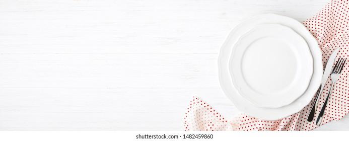 Plaques blanches vides et couverts sur serviette de table en bois blanc. Définition de la vue de dessus de table. Bannière pour le site web.