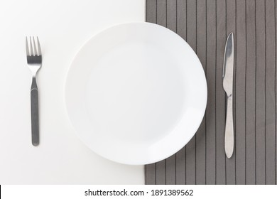 White empty plates set on the table with knives and forks and tablecloths. Ready to eat