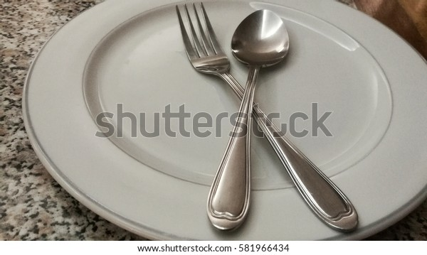 The white empty plates,spoon and fork waiting for served