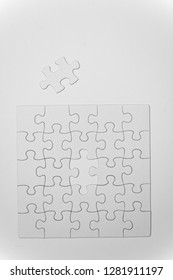 white, empty puzzles with a missing piece on a white background