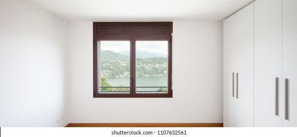 White empty room with windows overlooking the lake and large white wardrobe. Nobody inside