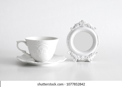 White empty round vintage photo frame with light grey color inside and a white tea cup, on white background. Clipping path inside the frame