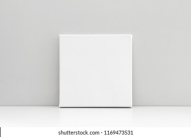 White empty square canvas on neutral gray background. Mock up poster, canvas template.