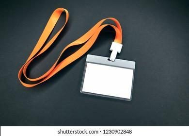 White empty staff identity mockup with orange lanyard. Name tag, ID card. Black background