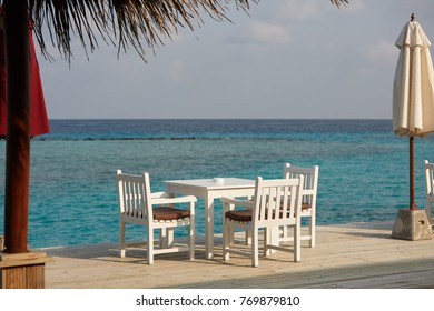 White empty table table and chairs at tropical resrraunt on open terrace in maldives. Blue ocean lagoon on background. No people.