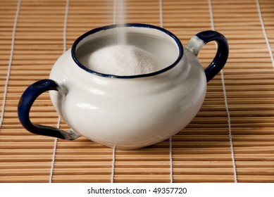 white enamel sugar bowl on a straw mat being filled