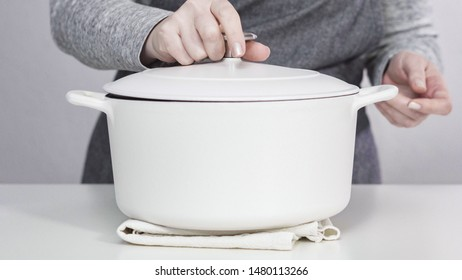 White enameled cast iron covered dutch oven on a white background.