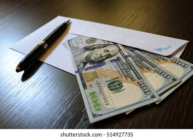 White envelope and 100 US dollar banknotes