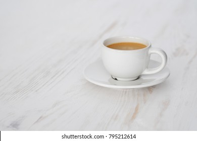 White espresso cup on wooden table. Low depth of field.
