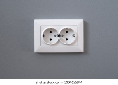 White european wall outlet on grey plaster wall with copy space. European interior outlet socket. Daylight.