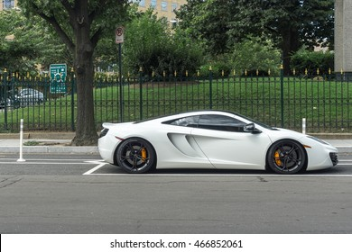 White exotic car parked on a city street