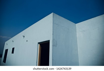 A white exterior parts of a building with blue sky background photo