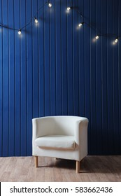 White fabric armchair on a background of blue wall with retro garland of light bulbs. Modern interior. Texture for the design