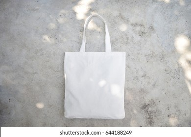 White fabric bag on cement background.