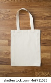 White fabric bag on wooden background