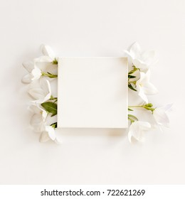 white fabric mock-up with blooming white bell flowers and leaves. flat lay, top view