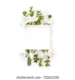 white fabric mock-up with blooming white bell flowers and leaves. flat lay, top view.