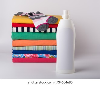 White fabric softener bottle and a stack of clean colorful clothes on white background.