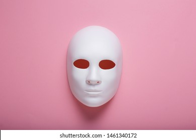 White face mask on pink background, hidden identity or fake influencer