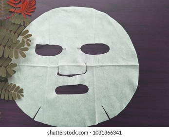white Face sheet On the wood table.natural leaf placed next to the mask.Moisturizes the skin.Facial treatment mask. Skin food for women. concept:Skin Care,beauty,White skin, Facial rejuvenation