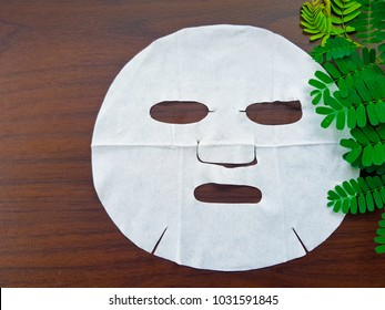 white Face sheet On the wood table.natural green leaf placed next to the mask.Moisturizes the skin.Facial treatment mask. Skin food for women. concept:Skin Care,beauty,White skin, Facial rejuvenation