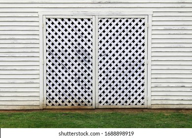 a white factory building barn with lattice wood door and grass