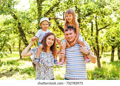 A White family of four with kids sitting on parents?? shoulders enjoying in a park on a sunny day