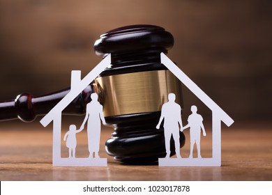 White Family Paper Cut Out In Front Of Judge Gavel On The Wooden Desk