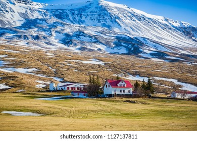 White farmhouse with bright red roof neaar Myvatn in Iceland