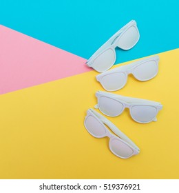 white fashion sunglasses in disco party style laid out on colored neon background.