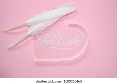 """White feathers on transparent glass heart, on pink background. The inscription """"One love"""". Space for text. Delicate postcard, Valentine card, declaration of love, wedding invitation."""