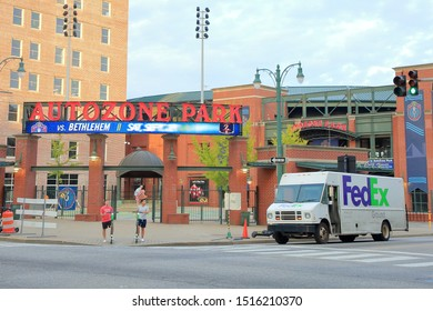 A white FedEx delivery truck passing by Autozone Park stadium. FedEx Corporation is NYSE publicly traded company with stock ticker FDX -  Memphis, Tennessee, USA - September 26, 2019