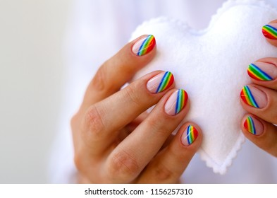 White felted heart in femaile hands with rainbow manicure. Love, valentine, lgbt, pride concept. Close up