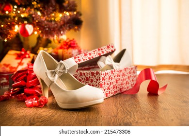 White female elegant shoes in a gift box with christmas tree and presents on background.