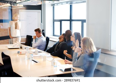 White female executive standing at head of conference room table leading a meeting with colleagues