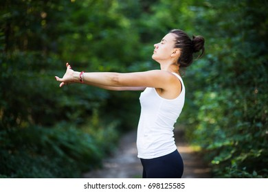 White female fitness model preparing for workout in the forest