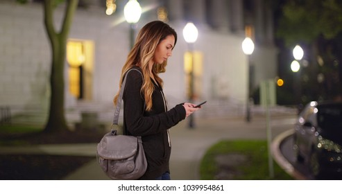 White female in her 20s messaging on cell phone standing outside campus library at night