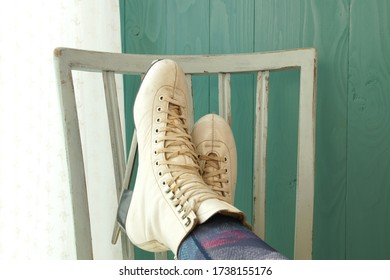 white female ice skating shoes on outstretched woman's legs on chair. Pair of Figure Ice Skates relaxing and propped up on an old vintage chair.