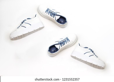 white female sneakers with blue  shoelaces isolated on white background. Flat lay, top view minimal background.