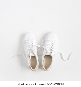 White female sneakers isolated on white background. Flat lay, top view