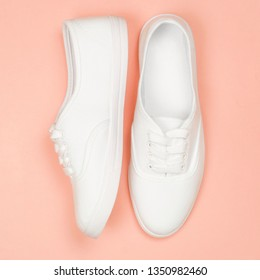 White female sneakers on coral background. Flat lay, top view minimal style