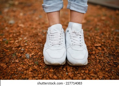 White female sneakers on walks in the park on a background of pebbles
