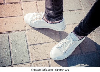 White female sneakers on walks in the park
