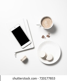 White feminine flat lay with beige macaroons, coffee and smartph