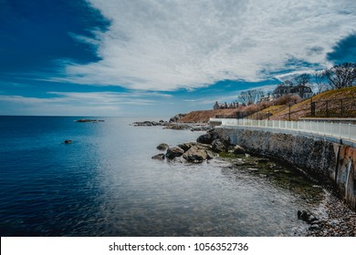 A white fence along the Cliff Walk off the beach at Newport, Rhode Island on a beautiful sunny day with picturesque clouds against a deep blue sky.