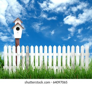 white fence with bird house and blue sky