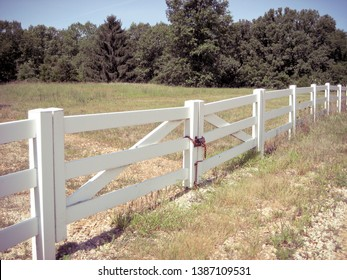 White Fence Bordering a Country Pasture with Trees