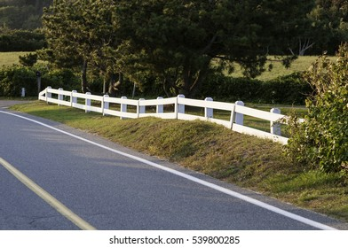 White fence bordering curve on Cape Cod